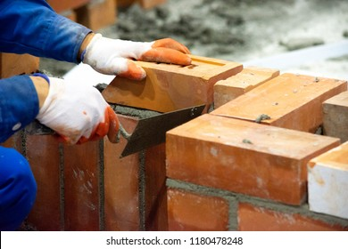 Bricklayer installing bricks, Bricklayer worker installing brick masonry on exterior wall with trowel putty knife
