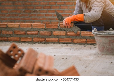 Bricklayer laying bricks to make a wall. professional construction worker laying bricks and building barbecue in industrial site. Detail of hand adjusting bricks.