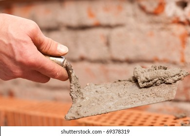 bricklayer laying bricks to make a wall, he is putting grout on top of bricks
