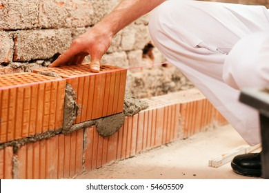 bricklayer laying, well, bricks to make a wall, he is pulling grout out of a joint with his trowel. This man is really working hard.