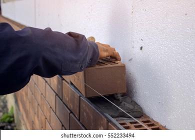 Bricklayer lays bricks under unravel. construction work