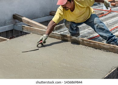 Bricklayer leveling a cement roof. Stretching out to smooth the casted concrete mix
