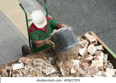 bricklayer mason worker depositing waste of bricks and tiles in rubble dumpster container in street city