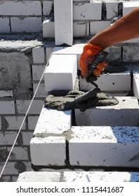 Bricklayer, masonry brick trowel in hand, mortar, brick.