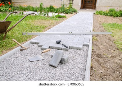 Bricklayer places concrete paving stone blocks for building up a patio, using hammer and spirit level