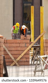 Bricklayer Preparing Laying Bricks On Wall
