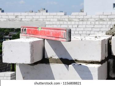 bricklayer puts a brick wall, masters, level