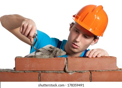 A bricklayer putting bricks being very concentrated