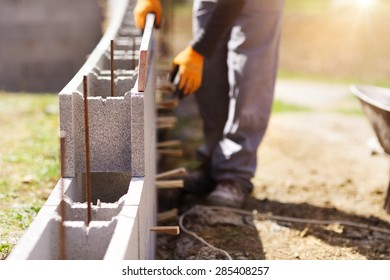 Bricklayer putting down another row of bricks in site