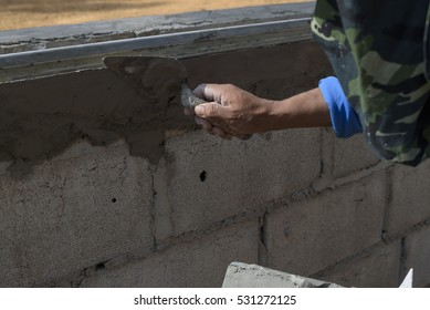 Bricklayer putting down another row of bricks