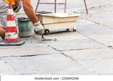 bricklayer repairing cobbled floor in urban square