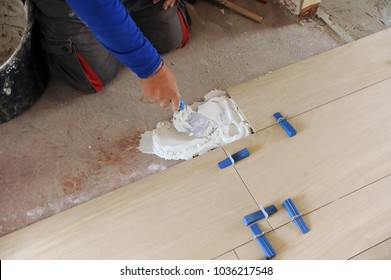 Bricklayer spreading white cement with trowel to place a new porcelain tile floor in the living room. Works of integral reform of the housing