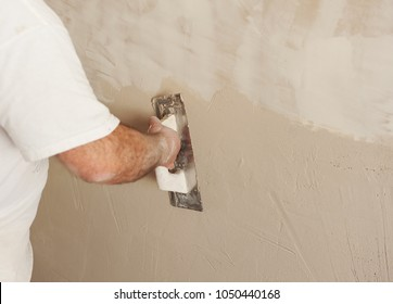 Bricklayer using the plastering trowel, wall plastered during house reform
