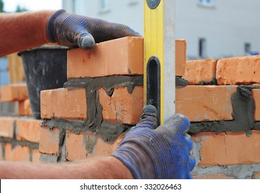 Bricklayer Using a Spirit  Level to Check New  Red Brick Wall Outdoor. Bricklaying Basics Masonry Techniques.