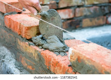 Bricklayer using trowel to tap a brick level. Hand white-wash cement built wall brick new house, Bricklayer worker installing brick masonry on exterior wall with trowel putty knife