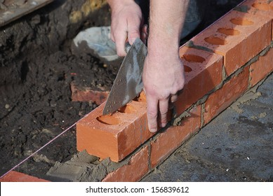 Bricklayer using trowel to tap a brick level