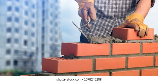 Bricklayer worker installing brick masonry
