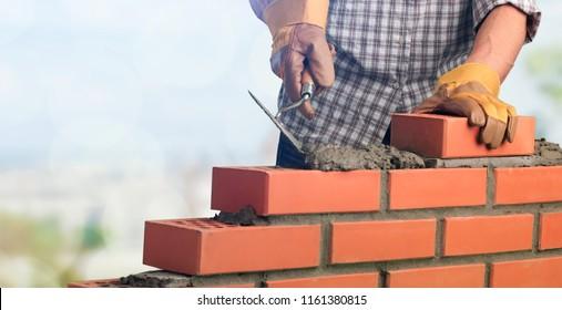 Bricklayer worker installing brick masonry