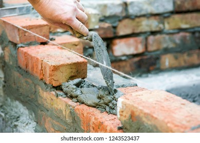Bricklayer worker installing brick masonry on exterior wall. Professional construction worker laying bricks. Bricklayer worker installing bricks on construction site