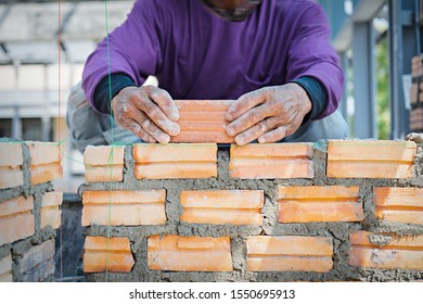 Bricklayer worker installing brick masonry on exterior wall with trowel putty knife for new house building at construction site.