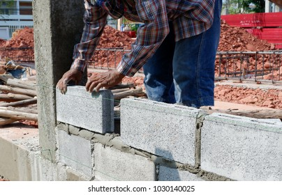 Bricklayer worker installing bricks at construction site