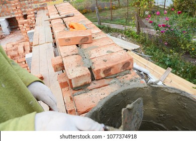 Bricklayer worker installing red blocks and caulking brick masonry joints exterior brick house  wall with trowel putty knife outdoor. Bricklaying.