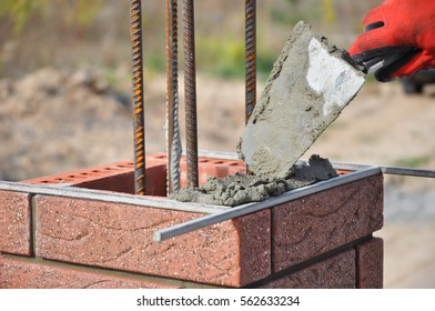 Bricklayer Worker Installing Red Clinker Blocks and Caulking Brick Masonry Joints Exterior Wall with Trowel putty Knife and Fixing with Spirit Level