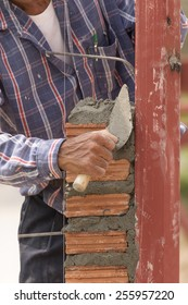Bricklayer working in construction site of  brick wall. Bricklayer putting down another row of bricks in site