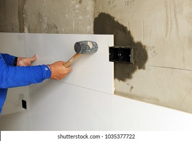 Bricklayer working with rubber hammer on the house reform, coating the kitchen with white tiles of porcelain stoneware