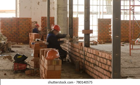 Bricklayers laying bricks to make a walls timelapse. professional construction worker laying bricks and building inside in industrial site. Detail of hand adjusting bricks.
