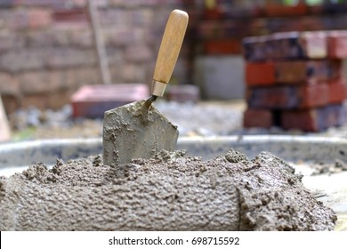 Bricklayers trowel in fresh mortar with bricks n the background
