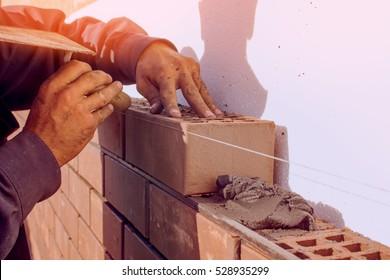 Bricklaying, construction work, manual labor.