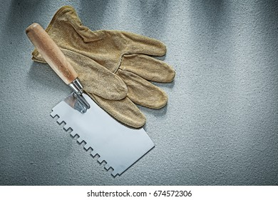 Bricklaying trowel leather protective gloves on concrete backgro