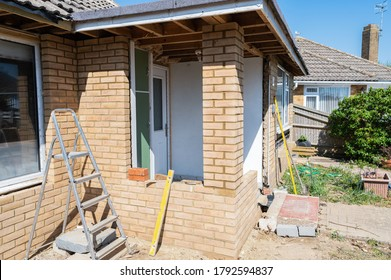 Bricklaying wall in residential property, unfinished front porch with no windows, renovation project, rows of bricks, selective focus