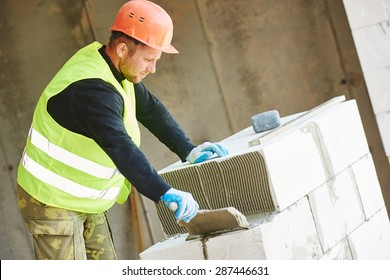Bricklaying work. construction worker mason bricklayer installing calcium silicate brick