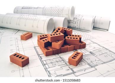 Steine zum Bau eines Hauses mit Konstruktionszeichnungen