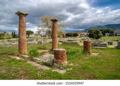 Brick's columns, in the distance - the ancient greek temple of Athena or Temple of Ceres, (c. 500 BC)  on a cloudy and sunny spring day in Archaeological Park of Paestum