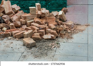 Bricks are on the pavement. Debris on the road. Unused bricks after construction. Broken bricks. Waste bricks. Garbage remained after construction. Texture of broken brick blocks