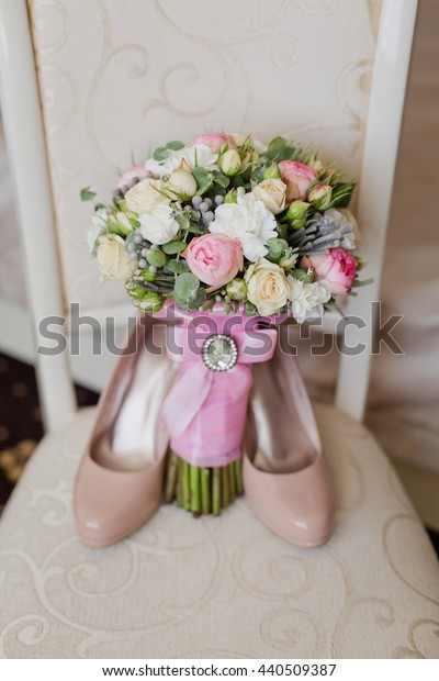 Bridal accessories: beige shoes and bride's bouquet