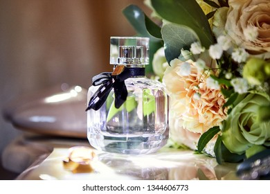 bridal accessories such as shoes, bouquet , ring and perfume lie on a table