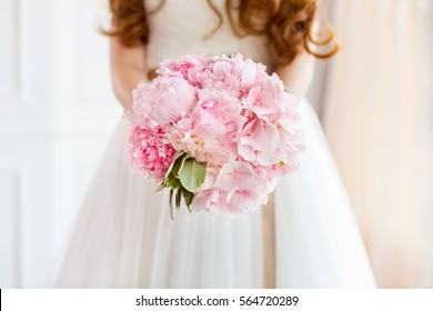 Bridal bouquet Beautiful of pink wedding flowers in hands of the bride. Close-up interior studio shot against bright background