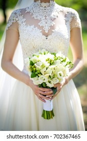 A bridal bouquet with callas, eustoma, berries in the bride's hands. Floristic composition.