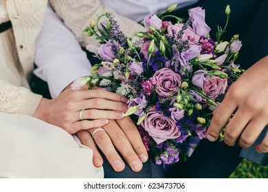 Bridal bouquet. Close-up flowers shot against bright background.  The girl in a white dress holds a beautiful bouquet of white, purple flowers. Beautiful flowers in hands of the bride. soft focus.