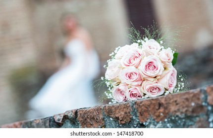 Bridal bouquet of flowers above a wall and a bride. Focus on the bouquet