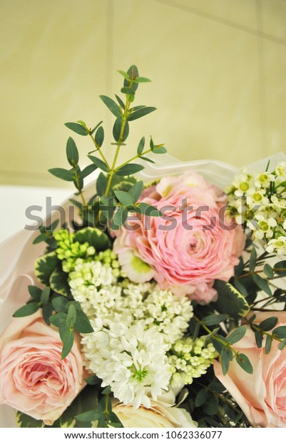 Bridal bouquet with light pink roses, white flowers and green brunches on blurred bright background. Vertical photo