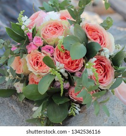 Bridal bouquet lying on the stones. Wedding bouquet of peach roses ,  single-head pink rose aqua, eucalyptus, ruscus, gypsophila