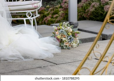 Bridal bouquet on the floor in front of the wedding dress