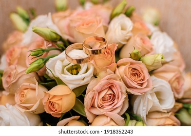 Bridal bouquet with orange roses. Gold wedding rings