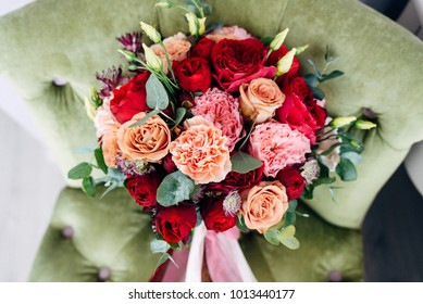 Bridal bouquet with a peach and red roses and long ribbons on green armchair