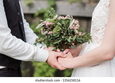 Bridal bouquet of pink and white flowers, roses and peonies, in the hands of a girl, wedding dress, the groom in a suit. Close-up of couple's hands.